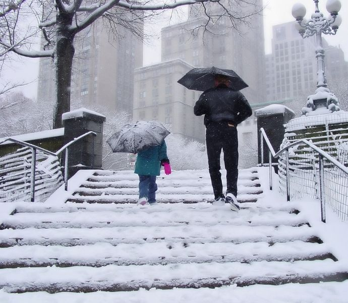 Two people walk up snowy stairs in a snowstorm, carrying umbrellas.