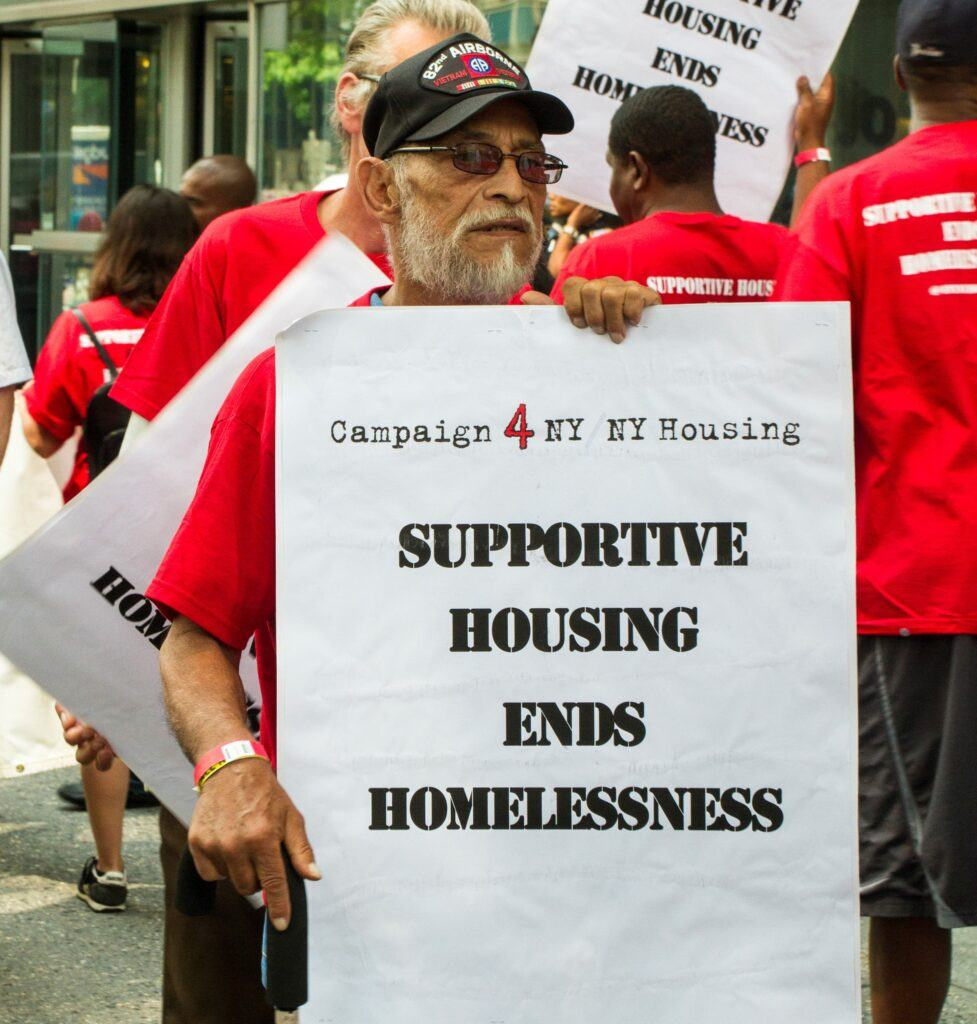an older man with a baseball cap and a red t-shirt holds a sign that says Supportive Housing Ends Homelessness, as part of a rally for the NY/NY Campaign