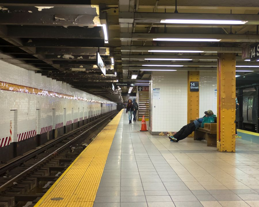 The inside of a subway terminal, a man is seen in the distance sleeping on a bench