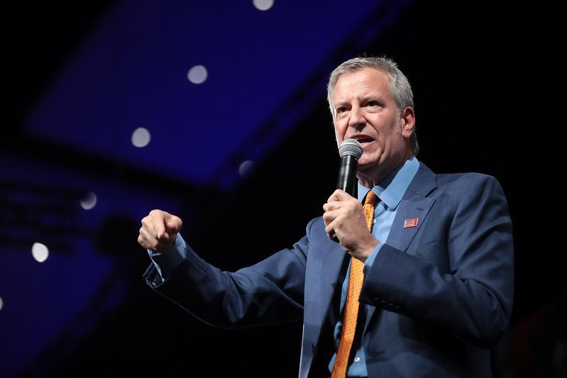 Mayor de Blasio, wearing a suit and yellow tie, speaks into a microphone. One of his hands is raised, pointing downward, and his face has an angry emotive expression.