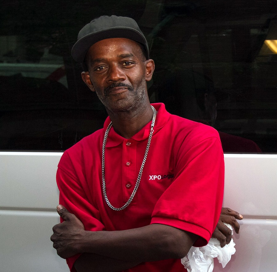 A man in a red-collared T-shirt with a blue baseball cap and a sliver chain leans against the side of the Coalition van, smiling softly at the camera with his arms crossed.