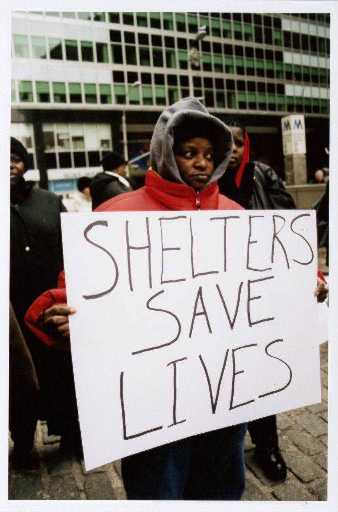 """A sepia-toned photograph of a person in a red puffy winter jacket holding a large sign that says """"Shelters Save Lives."""""""